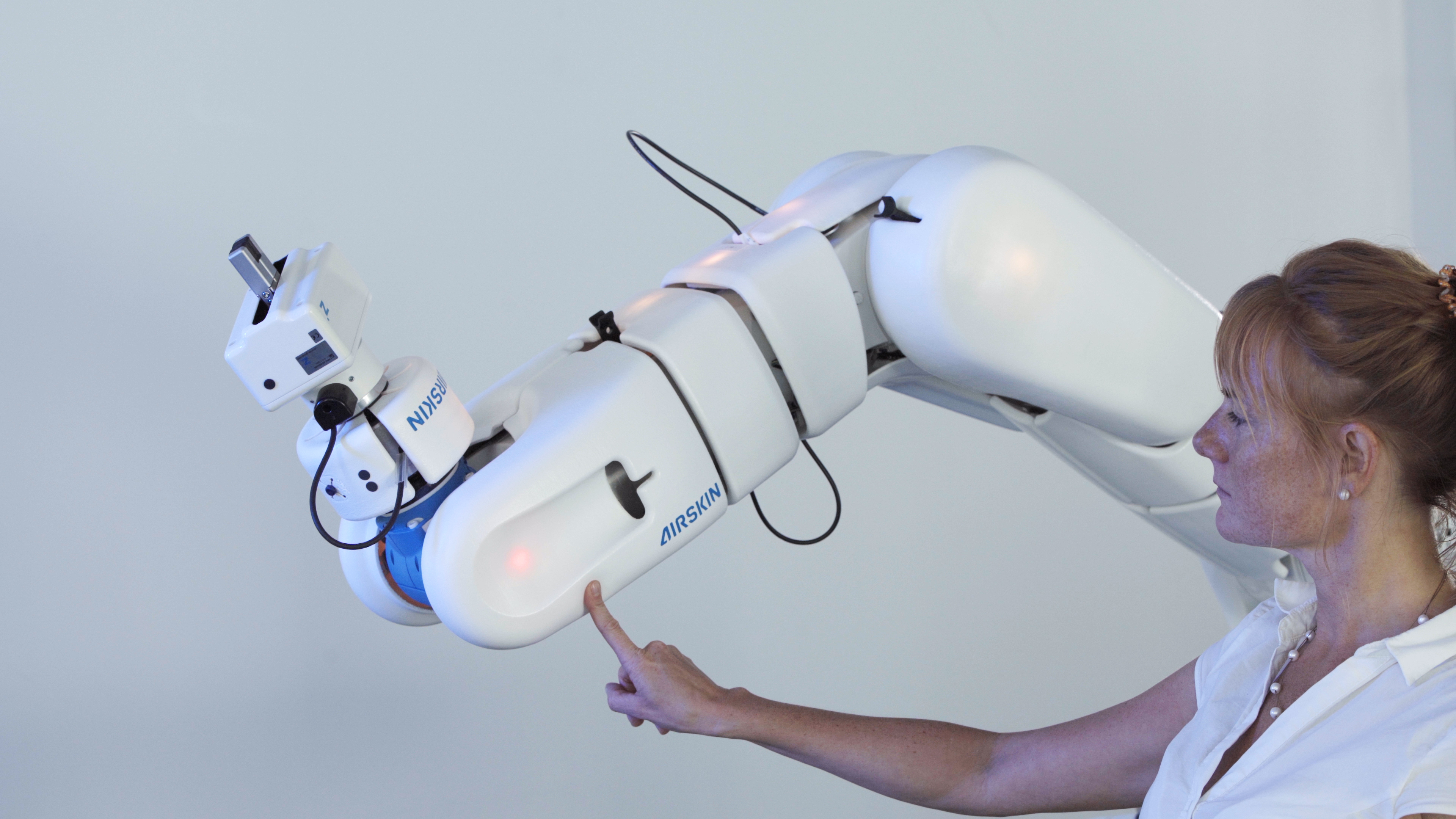 Girl touching industrial collaborative robot safely with her index finger
