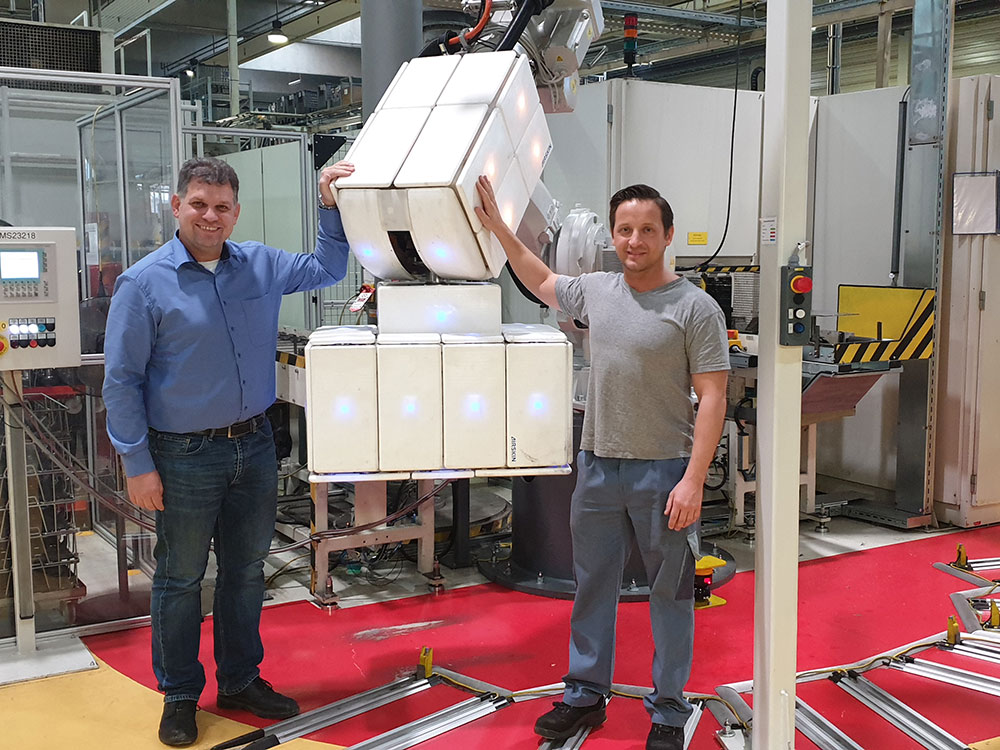 Fenceless collaborative robot covered with a robot safety skin and two human workers touching it