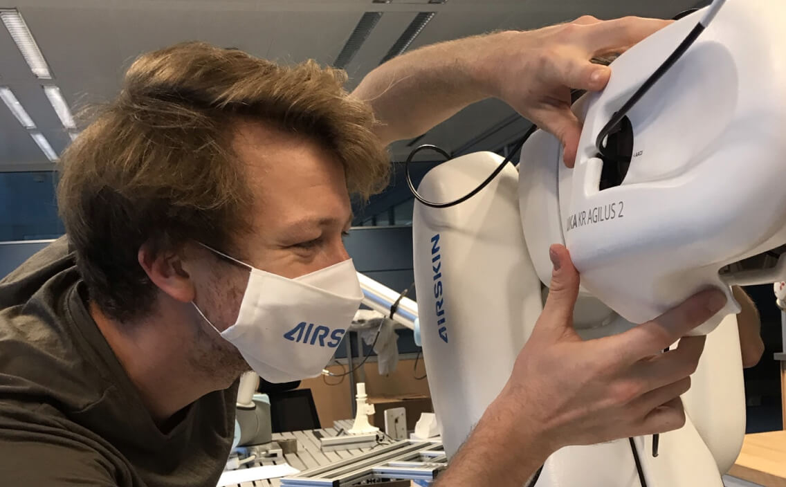 young man taking a close look at the agilus 2 collaborative robot covered with AIRSKIN