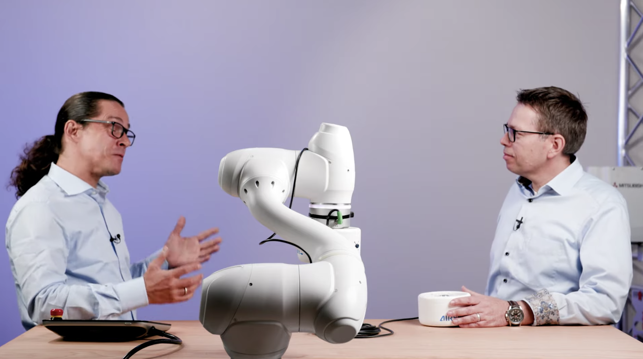Two men talking about a collaborative robot in a studio setting
