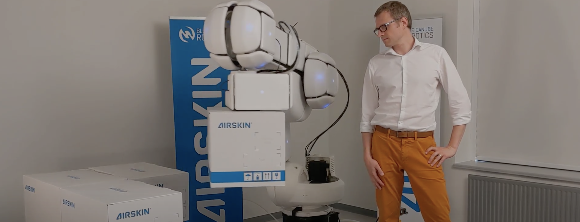 Robot with soft AIRSKIN and man studying the product